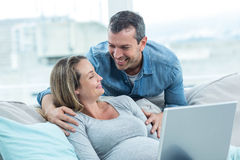 Couple using laptop in living room Stock Images