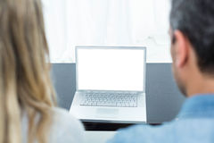 Couple using laptop in living room Royalty Free Stock Image