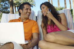 Couple Using Laptop And Mobile Phone Stock Photo