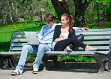 Couple using laptop outdoors Stock Photo