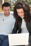 Couple using a laptop outdoors Royalty Free Stock Photo