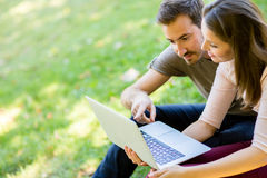 Couple using a laptop outdoors Royalty Free Stock Images