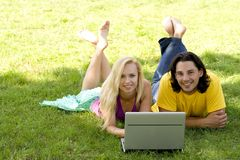 Couple using laptop outdoors Stock Image
