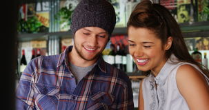 Couple using laptop in pub. Smiling couple using laptop in pub stock video footage