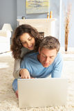 Couple Using Laptop Relaxing Laying On Rug At Home Royalty Free Stock Photo