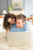 Couple Using Laptop Relaxing Laying On Rug At Home Royalty Free Stock Images