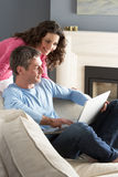 Couple Using Laptop Relaxing Sitting On Sofa Stock Photos