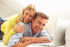 Couple Using Laptop Relaxing Sitting On Sofa Royalty Free Stock Photo