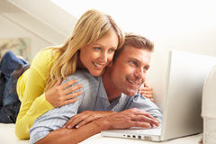 Couple Using Laptop Relaxing Sitting On Sofa royalty free stock images