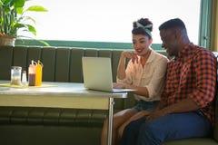 Couple using laptop in restaurant. Happy couple using laptop in restaurant Stock Photo