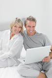 Couple using laptop sitting on bed looking at camera Royalty Free Stock Photos