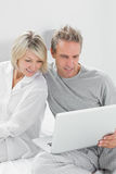 Couple using laptop sitting on bed Stock Photography