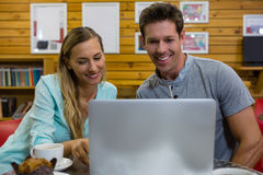 Couple using laptop while sitting in coffee shop Stock Photography