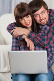 Couple using laptop while sitting on couch at home. Man embrace Royalty Free Stock Photography