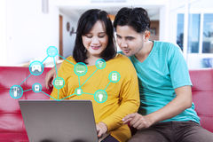 Couple using laptop with smart home system. Portrait of happy couple using laptop computer with smart home system while sitting on the sofa at home Stock Image
