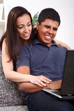 Couple using a laptop and smiling Stock Photography