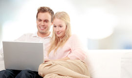 Couple using a laptop and smiling royalty free stock image