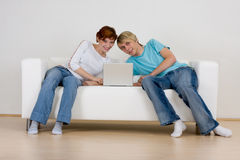 Couple using laptop on sofa. Closeup of young couple using laptop computer together on sofa indoors Royalty Free Stock Photography