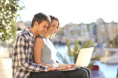 Couple using a laptop in a sunny coast town. Happy couple using a laptop in a sunny coast town street royalty free stock images