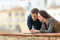 Couple using a laptop in a terrace on holiday royalty free stock image