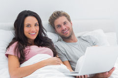 Couple using a laptop in their bed Royalty Free Stock Image