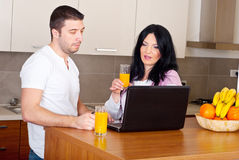 Couple using laptop in their kitchen Royalty Free Stock Photos