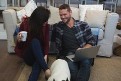 Couple using laptop with their pet dog in living room. At home stock photos