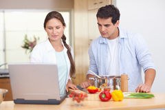 Couple using a laptop to cook Stock Images