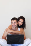Couple using a laptop together. Young Couple using a laptop at home Royalty Free Stock Photo