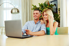 Couple using laptop together at home. Cheerful couple using laptop together at home Royalty Free Stock Images