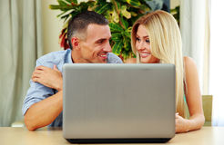 Couple using laptop together at home. Cheerful couple using laptop together at home Royalty Free Stock Image
