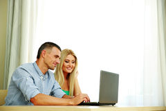 Couple using laptop together at home. Happy couple using laptop together at home Royalty Free Stock Photo