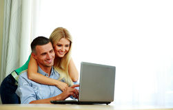 Couple using laptop together at home. Happy couple using laptop together at home Stock Photography