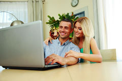 Couple using laptop together at home. Smiling couple using laptop together at home Stock Photo