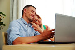 Couple using laptop together at home. Young couple using laptop together at home Royalty Free Stock Photo