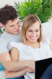 Couple using laptop together lying on sofa Royalty Free Stock Images