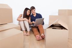 Couple using laptop together in new home Stock Photos