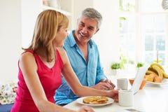 Couple Using Laptop Whilst Having Breakfast In Kitchen Stock Photos