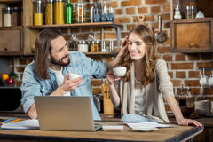 Couple using laptop. Young smiling couple drinking coffee and talking while using laptop at home Royalty Free Stock Images