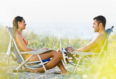 Couple using laptops at beach Royalty Free Stock Image