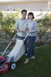 Couple Using The Lawn Mower Stock Photo
