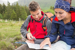 Couple using map and compass to find the way Royalty Free Stock Photo