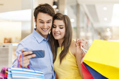 Couple using mobile devices in shopping mall Stock Image