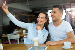 Couple using mobile phone at cafe Stock Photography
