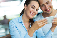 Couple using mobile phone at cafe Stock Photo