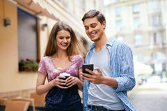 Couple Using Mobile Phone And Drinking Coffee Outdoors Royalty Free Stock Image