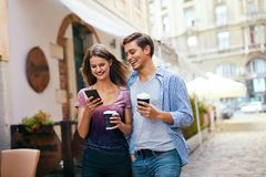 Couple Using Mobile Phone And Drinking Coffee Outdoors Royalty Free Stock Images