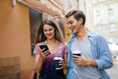 Couple Using Mobile Phone And Drinking Coffee Outdoors Stock Photography