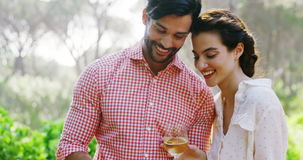 Couple using mobile phone while having glass of drink stock footage