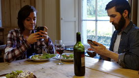 Couple using mobile phone while having meal. At home stock video